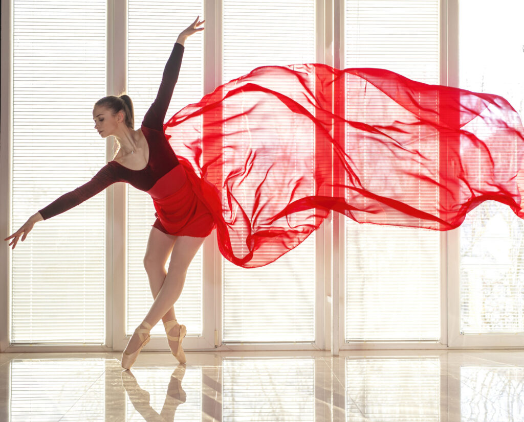 Beautiful young focused ballerina in elegant long red ballet dress in butterfly pose stands in front of big round shaped window at ballet studio while natural daylight illuminates interior with ambient light