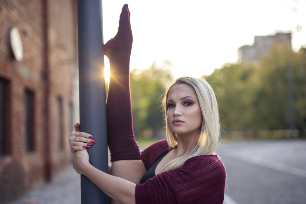 Blonde young pretty girl dancer perform in empty street leaning on pole