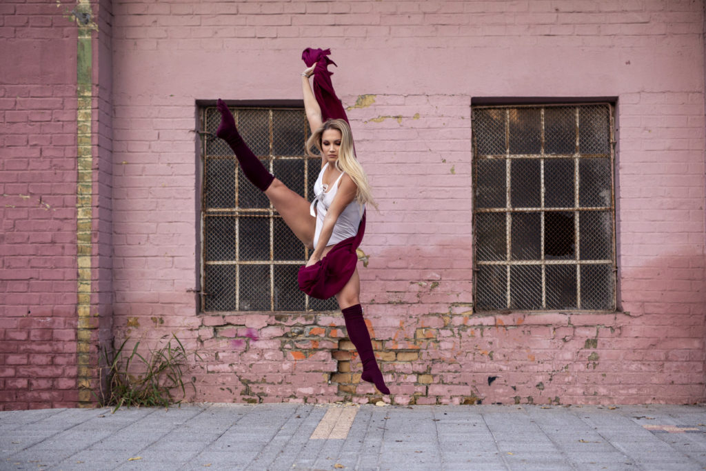 Beautiful young woman make performance on stret, she jump in front of window in old part of town