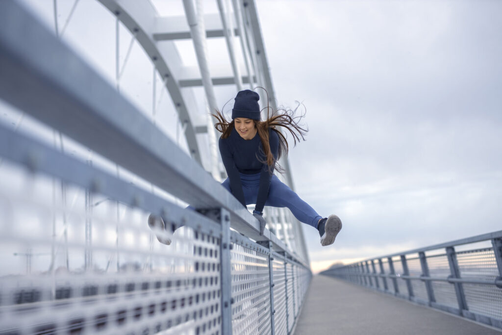 Young happy fitness woman in winter blue sportswear train agility while skips bridge fence during cold winter day